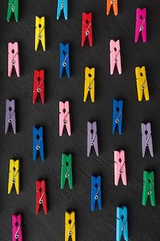 Mollette multicolori sulla superficie nera. vista dall'alto. cornice verticale.