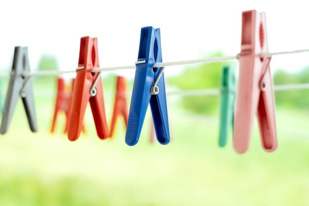 Mollette multicolori per asciugare la biancheria pulita appese in natura su una corda da bucato bianca