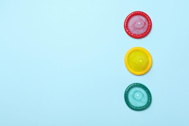 Preservativi multicolori sulla parete blu, spazio per il testo