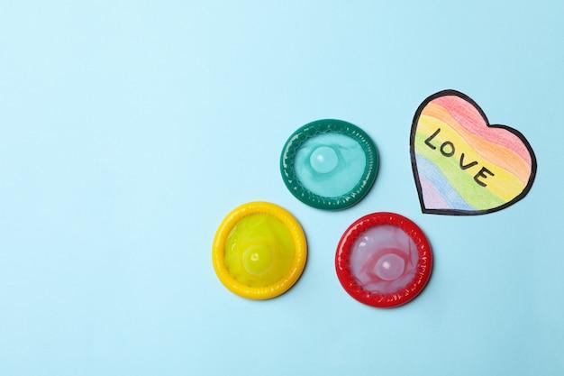 Preservativi multicolori e cuore nei colori lgbt con testo love sulla superficie blu