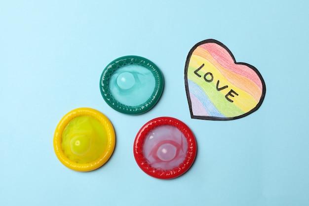 Preservativi multicolori e cuore nei colori lgbt con testo love sulla parete blu