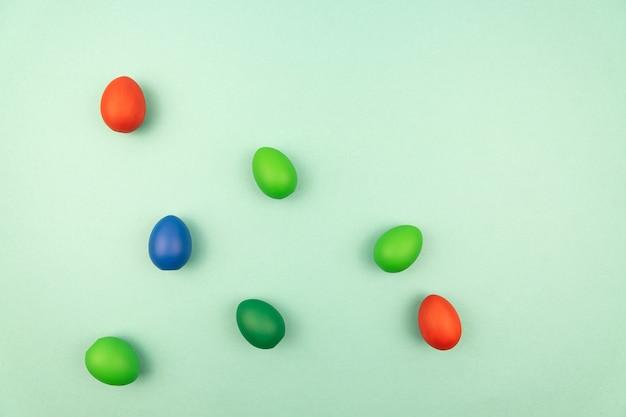 Uova di pasqua multicolori su sfondo azzurro con spazio di copia.