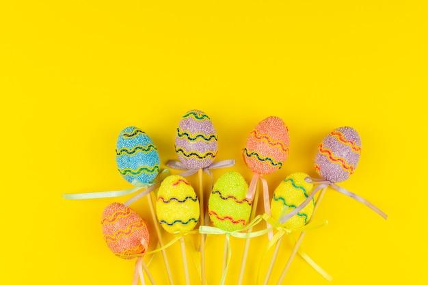 Uova di pasqua multicolori su bastoni su sfondo giallo. cartolina d'auguri festiva di festa di pasqua con lo spazio della copia.