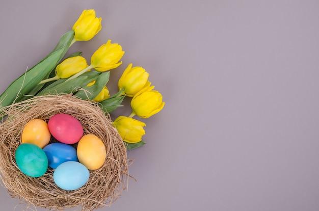 Uova di pasqua multicolori con un mazzo di tulipani gialli su sfondo grigio, con spazio di copia