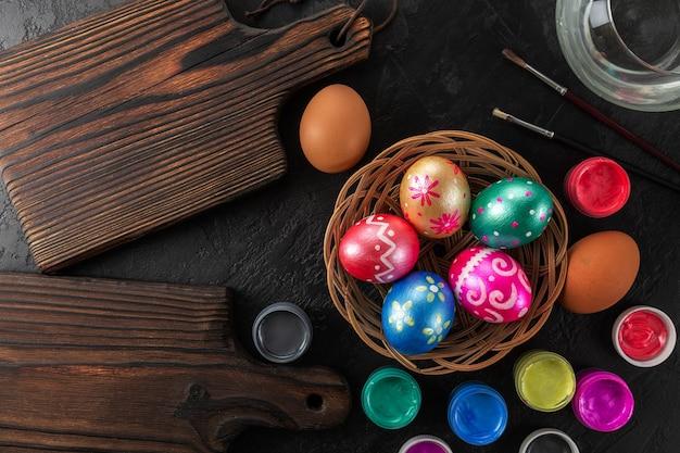 Pasqua multicolore dipinte a mano uova, vernici e pennelli.