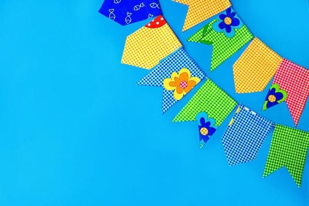 Bandiere in tessuto multicolore su sfondo blu. decorazioni per la vacanza.