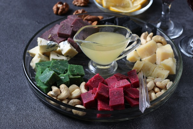 Formaggio gourmet multicolore, olive, noci, miele e fette di limone su sfondo scuro. antipasto per una festa del vino. avvicinamento