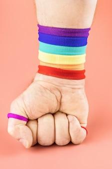 Mano multicolore serrata a pugno su superficie colorata concetto lgbtq