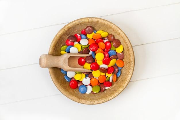 Caramelle di cioccolato a guscio duro multicolore in una ciotola di legno su un tavolo bianco in una vista dall'alto