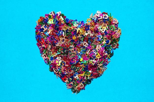 Lettere multicolori dell'alfabeto inglese disposte a forma di cuore su un blu