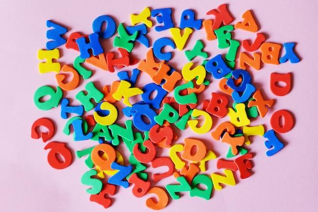 Lettere multicolori dell'alfabeto inglese mescolate sul rosa