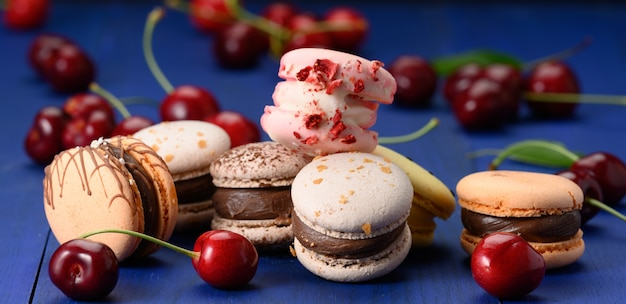 Macarons multicolori e ciliegie rosse mature su fondo di legno blu, fine su