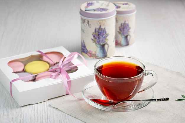 Amaretti multicolori in una scatola e una tazza di tè su un tavolo da cucina in legno chiaro tè del mattino e dolci