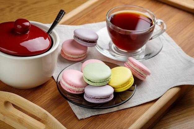 Amaretti multicolori e una tazza di tè su un vassoio di legno tè mattutino e dolci
