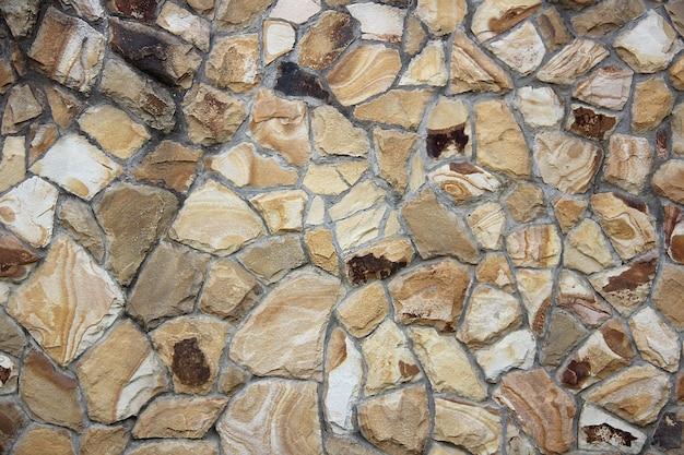 Priorità bassa di struttura della parete di roccia gialla e marrone multicolore e multi-dimensioni