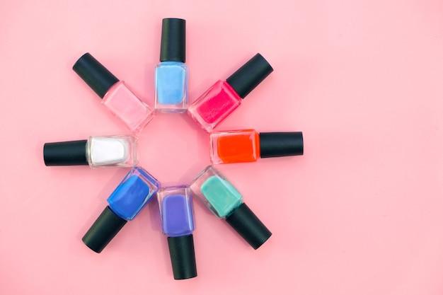 Smalti multicolori su sfondo rosa. concetto di manicure