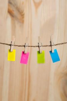 Note di carta multicolore appese con mollette sulla corda. copia spazio. posto per il tuo testo. cornice verticale.