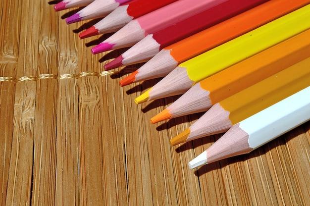 Matite multicolori disposte in fila su un tavolo di legno.
