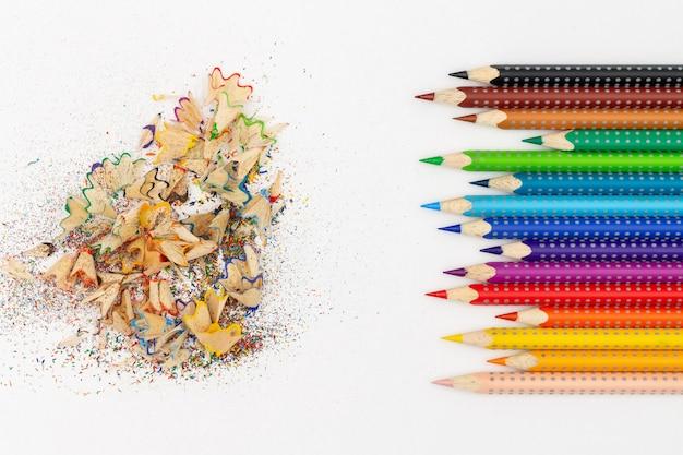 Matite multicolori su uno sfondo chiaro accanto alla pialla e trucioli di matita.