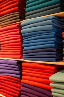 Pezzi multicolori di vestiti piegati in uno scaffale e ordinati per gamme di colori. piazza del mercato