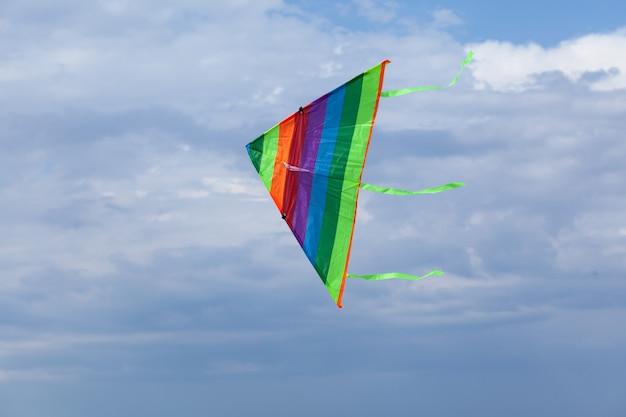 Un aquilone arcobaleno multicolore si libra nel cielo sullo sfondo delle nuvole