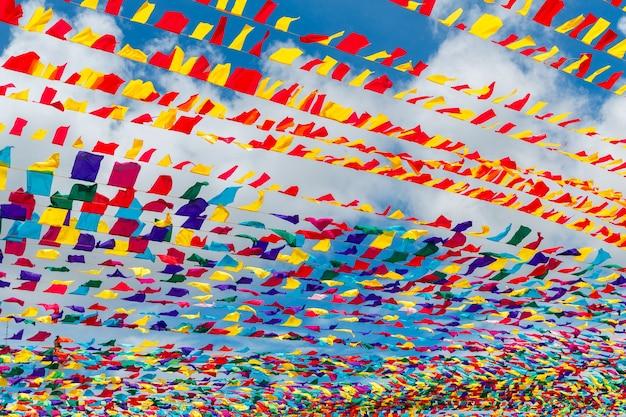 Nastri multicolori contro la decorazione festiva del cielo blu delle strade della città per la festa di primavera...