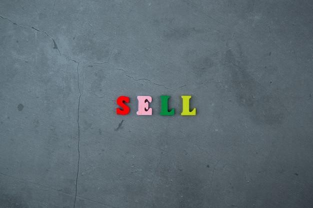 La parola di vendita multicolore è composta da lettere di legno su una superficie della parete intonacata grigia.