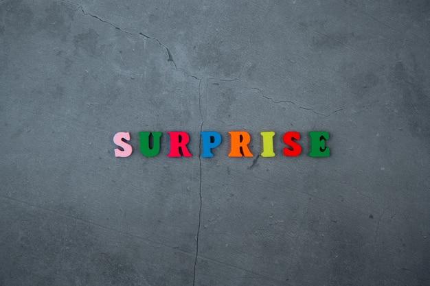 La parola sorpresa multicolore è composta da lettere di legno su una superficie della parete intonacata grigia.