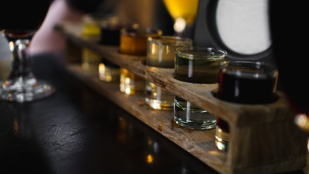 Cocktail trasparenti multicolori, una serie di scatti in una riga, sei porzioni su un supporto di legno, substrato. bevande per il menu ristorante, bar, caffetteria