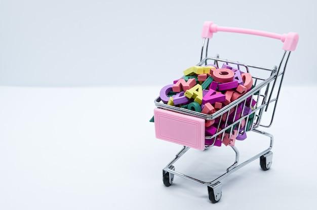 Lettere in legno multicolore in un carrello per supermercati in metallo su uno sfondo bianco. concetto: ritorno a scuola, alfabetizzazione, lettura, apprendimento delle lingue. spazio per il testo