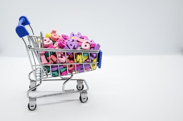 Numeri di legno multicolori in un carrello per supermercati in metallo su sfondo bianco. concetto: ritorno a scuola, matematica, aritmetica, imparare a contare. spazio per il testo