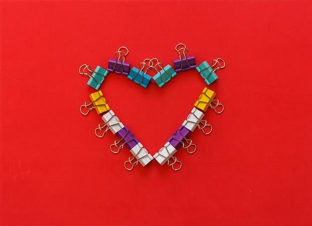 Graffette per ufficio in metallo multicolore che formano forma di cuore su sfondo rosso. concetto di san valentino.