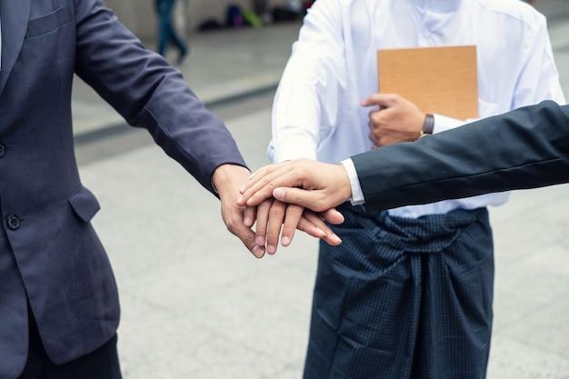 Uomo d'affari multiculturale che impila le mani insieme della cooperazione di accordi commerciali in ambito urbano. unità e concetto di lavoro di squadra