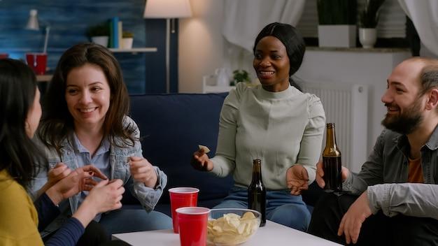 Amici multiculturali che ridono mentre condividono consigli sullo stile di vita seduti sul divano a tarda notte in li...