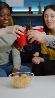 Amici multiculturali che socializzano seduti sul divano in soggiorno a tarda notte