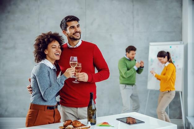 Gruppo multiculturale di colleghi che celebrano il successo nella sala riunioni