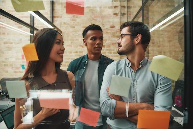 Team multiculturale allegro colleghi maschi e femmine che pianificano il processo di lavoro e utilizzano colori
