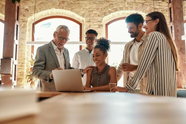 Team multiculturale che guarda il laptop e discute di qualcosa mentre si lavora insieme in ufficio