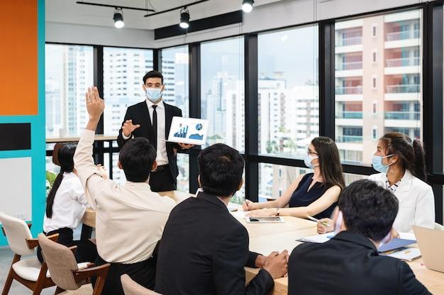 Riunione d'affari multietnica con presentazione dell'uomo d'affari del piano aziendale con il computer portatile
