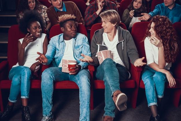 Azienda multietnica di amici che mangiano popcorn nel cinema.
