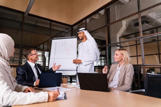 Riunione multietnica del team aziendale aziendale in ufficio per un piano di marketing strategico - impiegati, imprenditori e dipendenti dell'azienda al lavoro in una società multinazionale