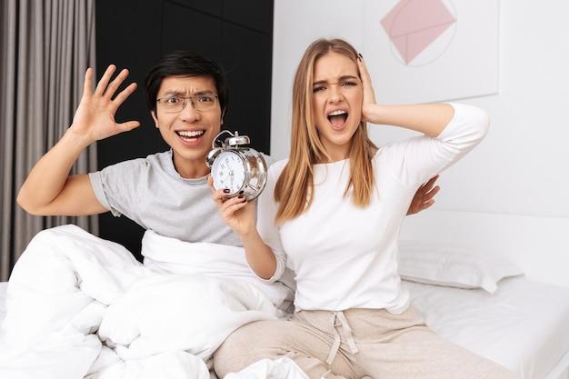Coppia multietnica, uomo e donna sdraiati insieme a letto a casa e tenendo sveglia