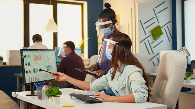Colleghi multietnici con maschere di protezione che controllano le statistiche annuali che guardano i grafici nel computer e negli appunti, donna di colore che prende appunti sul tablet. lavoro di squadra diversificato nel rispetto della distanza sociale.