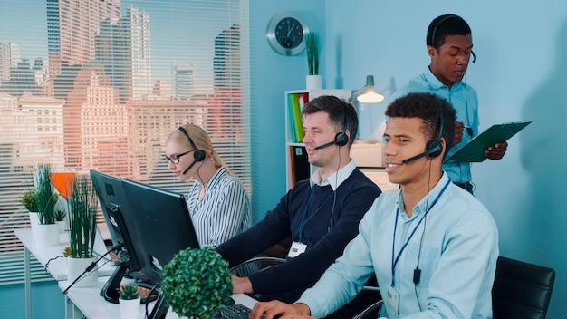 Rappresentante multietnico del servizio clienti che racconta una barzelletta ai suoi colleghi mentre chiama il cliente...