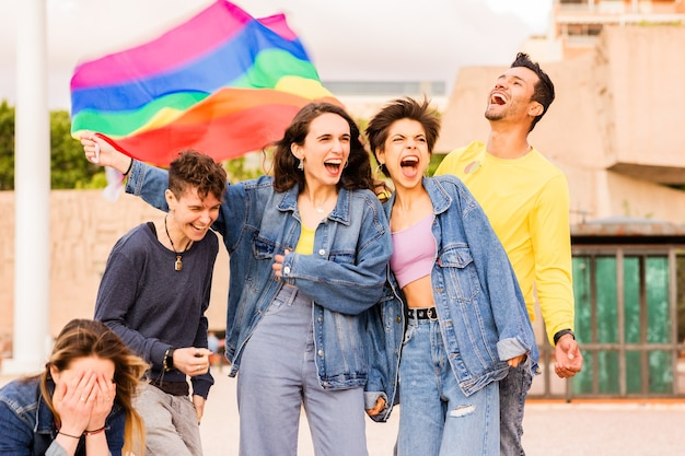 Gruppo lgbtq di diversità multietnica con amici della bandiera arcobaleno per l'espressione di genere e l'orgoglio dell'identità...