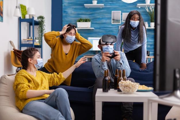 Amici multietnici che si godono la tecnologia vr giocando ai videogiochi in soggiorno indossando una maschera per prevenire l'infezione da coronavirus mantenendo le distanze sociali. diverse persone che si divertono alla nuova festa normale