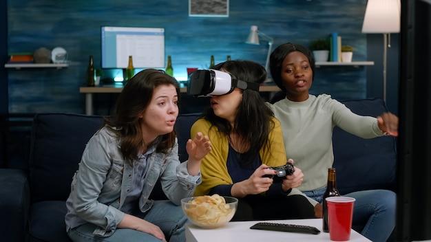 Amici multietnici che sperimentano la realtà virtuale perdendo videogiochi indossando cuffie vr durante la competizione di gioco. gruppo di persone di razza mista che escono insieme divertendosi a tarda notte nel soggiorno
