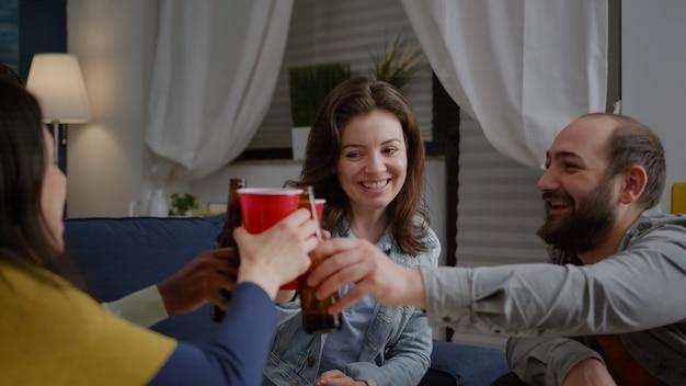 Amici multietnici che si riuniscono a tarda notte in soggiorno mentre riposano sul divano acclamando le bottiglie di birra durante la festa in casa. gruppo di persone di razza mista che si divertono a trascorrere del tempo insieme