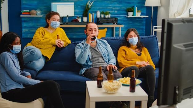 Amici multietnici che guardano la tv, si rilassano, trascorrono del tempo insieme indossando una maschera protettiva seduta sul divano durante l'epidemia di pandemia di covid. godendo la festa bevendo birra e mangiando patatine.