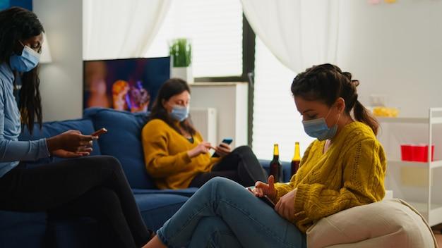 Amici multietnici che si rilassano sul divano alla ricerca sui telefoni, socializzano godendosi il tempo libero insieme indossando maschere di protezione e mantenendo la distanza sociale contro la pandemia di coronavirus prevengono la diffusione del virus